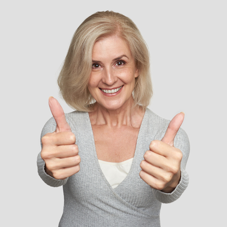 Excited mature woman showing thumbs up. Studio portrait
