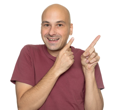 Cheerful bald man pointing finger. Isolated