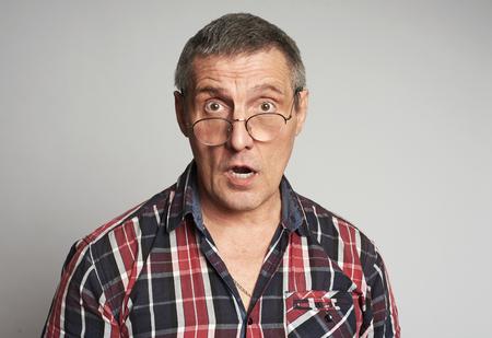 Surprised senior man portrait wearing glasses isolated on gray background 版權商用圖片