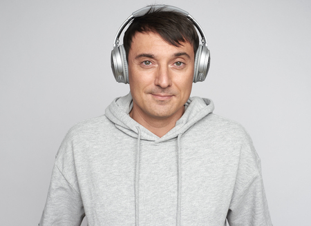 Handsome man listening to musicisolated on grey background