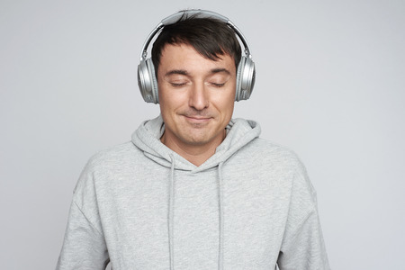 handsome man in headphones listening to music. Isolated on grey studio wall