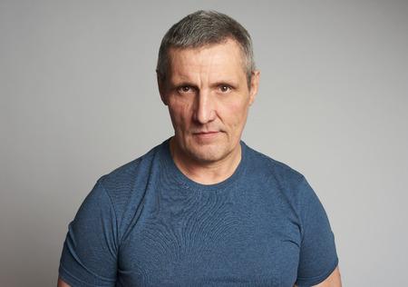 Hombre guapo de 50 años aislado sobre fondo gris