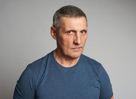 Älterer Mann im blauen T-Shirt auf grauem Hintergrund isoliert Standard-Bild