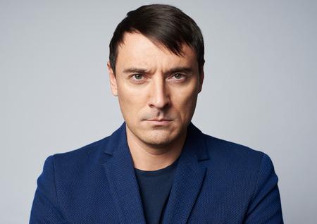 Hombre guapo de mediana edad con expresión seria en su rostro. Tiro del estudio