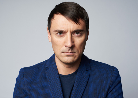 Middle aged handsome man with serious expression on his face. Studio shot