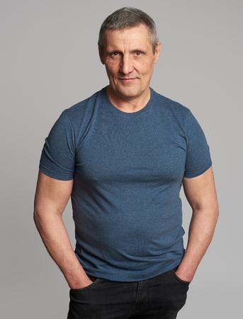 50 Jahre Mann in Freizeitkleidung. Schöner Kerl lächelt isoliert auf grauem Studiohintergrund Standard-Bild