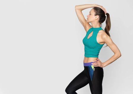 sporty girl is doing exercise isolated over grey studio wall