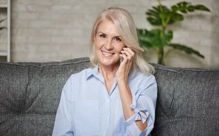 Happy 50 years old woman is talking on phone at home Imagens