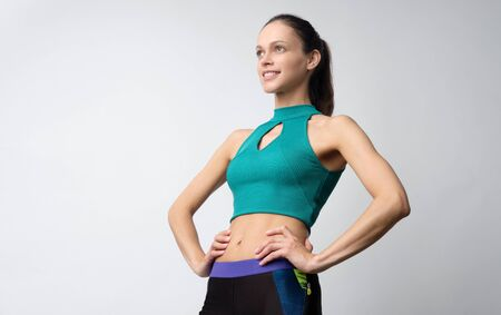 Sporty pretty woman is wearing sport clothes isolated on grey background