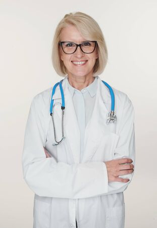 Friendly senior woman doctor is smiling. Isolated on white Stock Photo