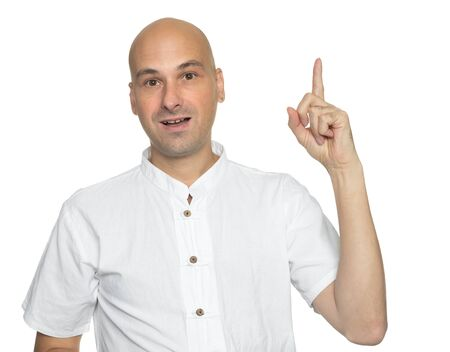 Bald man is pointing upwards in studio and looking at camera. isolated on white background