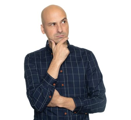 thoughtful bald man with hand on chin is looking away isolated on white