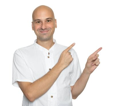 Happy handsome bald man in casual shirt pointing away and smiling while standing against white background