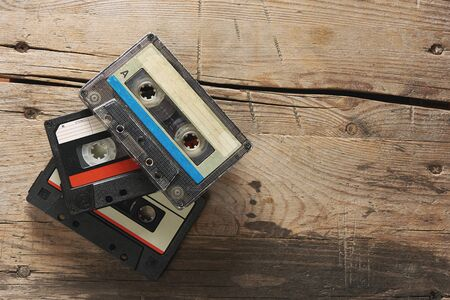 Old audio tape compact cassettes on wooden background. top view with copy space
