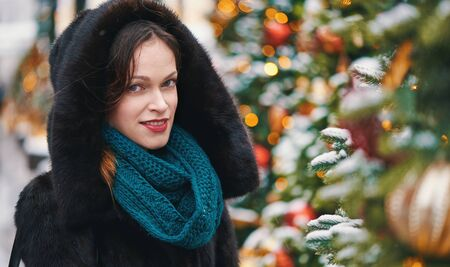 Happy young woman near the Christmas treeon a street. New year