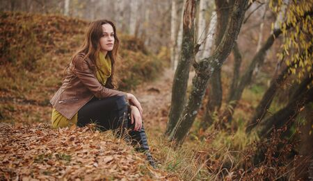 Pretty woman is sitting on a grass in the autumn park