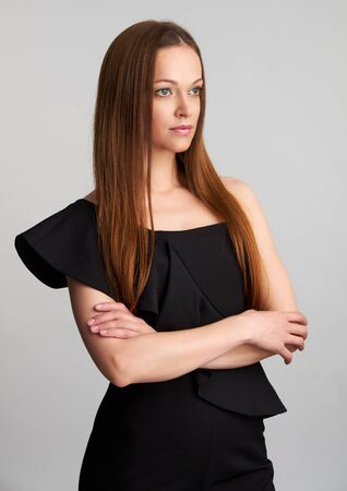 Beautiful woman with straight brown hair. Isolated on grey background Stockfoto