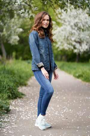 Happy smiling retty girl is standing in the garden. Brunette woman wearing denim clothes
