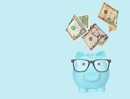 Piggy bank with glasses isolated on a blue background.