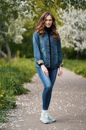 Beautiful brunette woman with curly hair in the spring garden. Full length outdoor portrait Standard-Bild