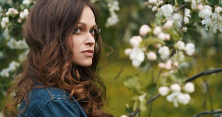 Beautiful brunette woman with curly hair in the spring garden. Outdoors portrait
