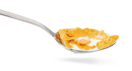 Cornflakes in a spoon. Corn flakes with milk isolated on white background. Clipping path
