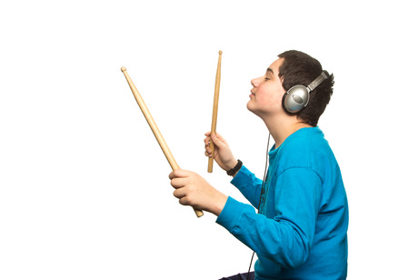 Boy with headphones and drumsticks isolated on white