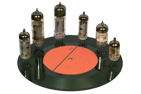 Six multi-sized vacuum tubes stand on the surface of the old vinyl disc. Stock Photo - 2374928