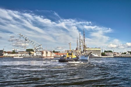 Sailing ships and towboat in the port Stock Photo - 5537147