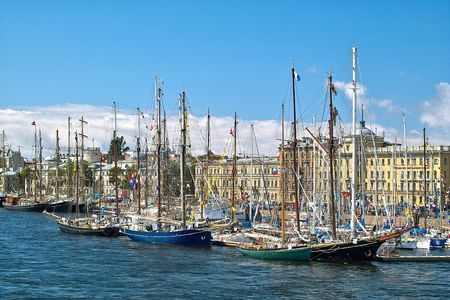 Tallships and yachts in front of antique buildings