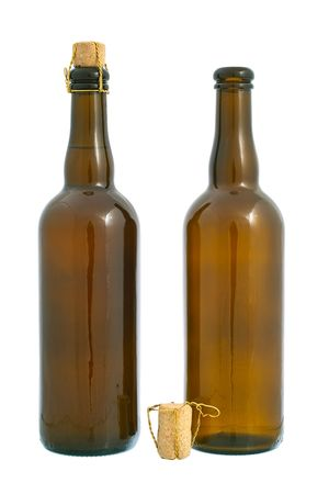Two dark glass beer bottles and cork with golden wire. Isolated on white background photo