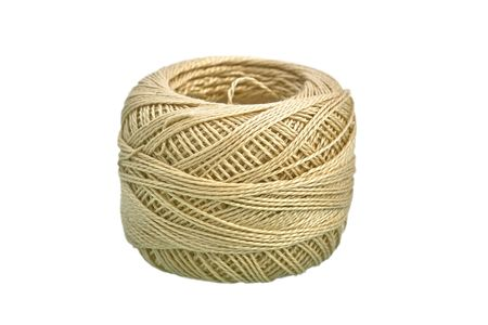 Clew of beige cotton yarn macro image on white background