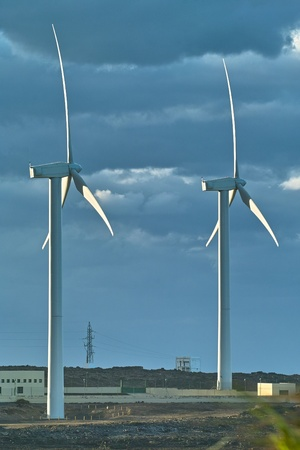 Two white windmills in the strong wind