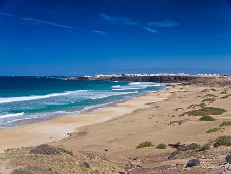moresque: Ocean, sand and  small white town an the rocky shore