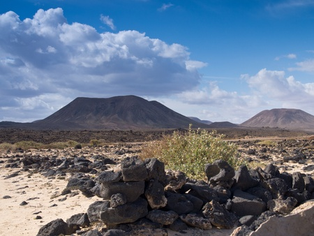 Stony desert and volcanic hills under dramatical cloudy sky