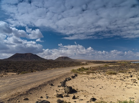 Country road through the stony desert and volcanic hills under dramatical cloudy sky Stock Photo - 9688227