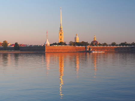 Key view of the Peter and Paul fortress across the Neva River reflected in quiet water at sunrise morning. The original citadel of Saint Petersburg, Russia, founded by Peter the Great in 18th century Stock Photo - 47131109