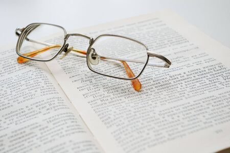 narrate: glasses on  an open book Stock Photo