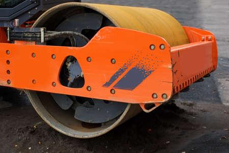 steamroller: orange steamroller on a pile of wet sand