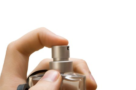 finger pressing the sprayer on perfume bottle photo
