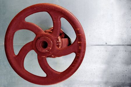 red rusty gauge wheel on silver background photo