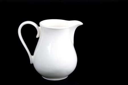 creamer: white porcelain creamer pitcher isolated on black