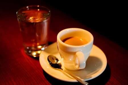 cup of espresso served in traditional way with the glass of water (warm tungsten light)