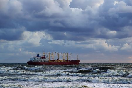 cargo vessel in the stormy sea under the cloudy skies Stock Photo