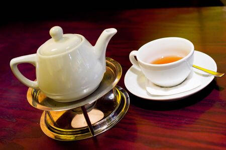 set of teapot and cup under warm cafe light Stock Photo