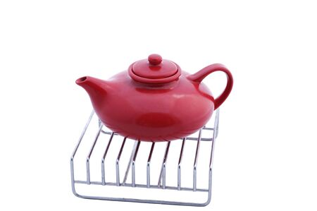 trivet: red teapot on the  stainless steel grill Stock Photo