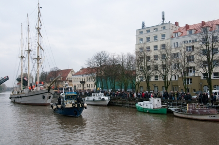 oldtown: KLAIPEDA, LITHUANIA – NOVEMBER 10: Klaipeda city symbol barquentine Meridianas after pass of  the first drawbridge on the way to the major overhaul  as crowd greets her passage on November 10, 2012 in Klaipeda. Editorial