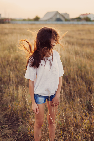 beatitude: Young girl with long brown hair stay at the meadow. Her hair fluttering in the wind. Selective focus, warm tinted. Stock Photo