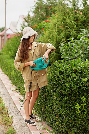 Cute girl with long hair cutting boxwood with electrical hedge trimmer. She is wearing a straw hat and work clothes. Stock Photo