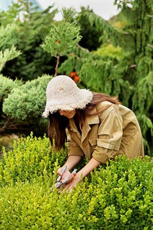 Girl gardener in working clothes and straw hat cuts garden scissors evergreen. Her face is hidden.